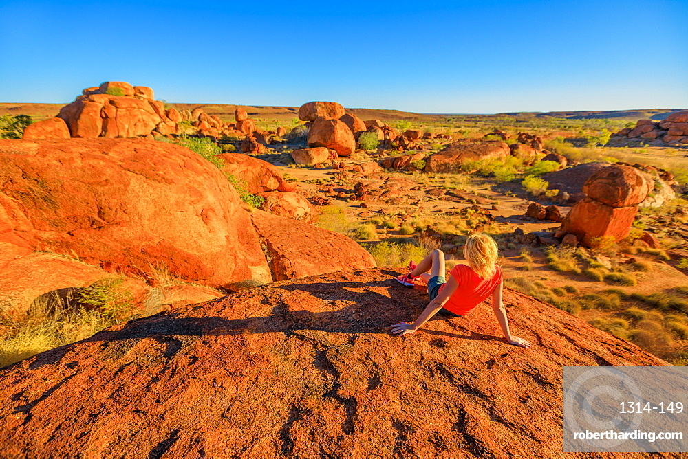 Tourist woman on the top view of Karlu Karlu (Devils Marbles) Conservation Reserve looking at panorama of granite boulders and rock formations at sunset, Outback, Northern Territory, Australia, Pacific