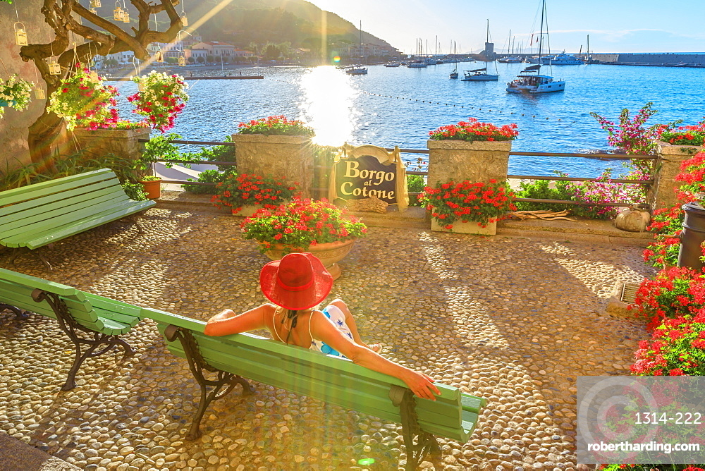 Elegant woman in red with hat at Marciana Marina waterfront, the flowery old district called Borgo al Cotone. Caucasian tourist on holiday travel in Italy. Marciana Marina in summertime on Elba island