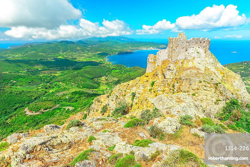 Iconic view of Volterraio Castle on rock at 394 m. Fortress of Volterraio, symbol of Elba Island, dominates Portoferraio Gulf. Panoramic landscape with view from top of Elba mountain. Tuscany, Italy.