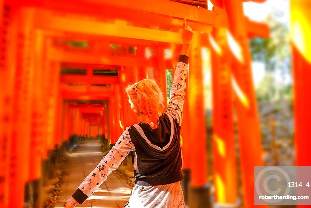 Woman walking beneath red torii gates at Fushimi Inari Shinto shrine, Kyoto, Japan, Asia