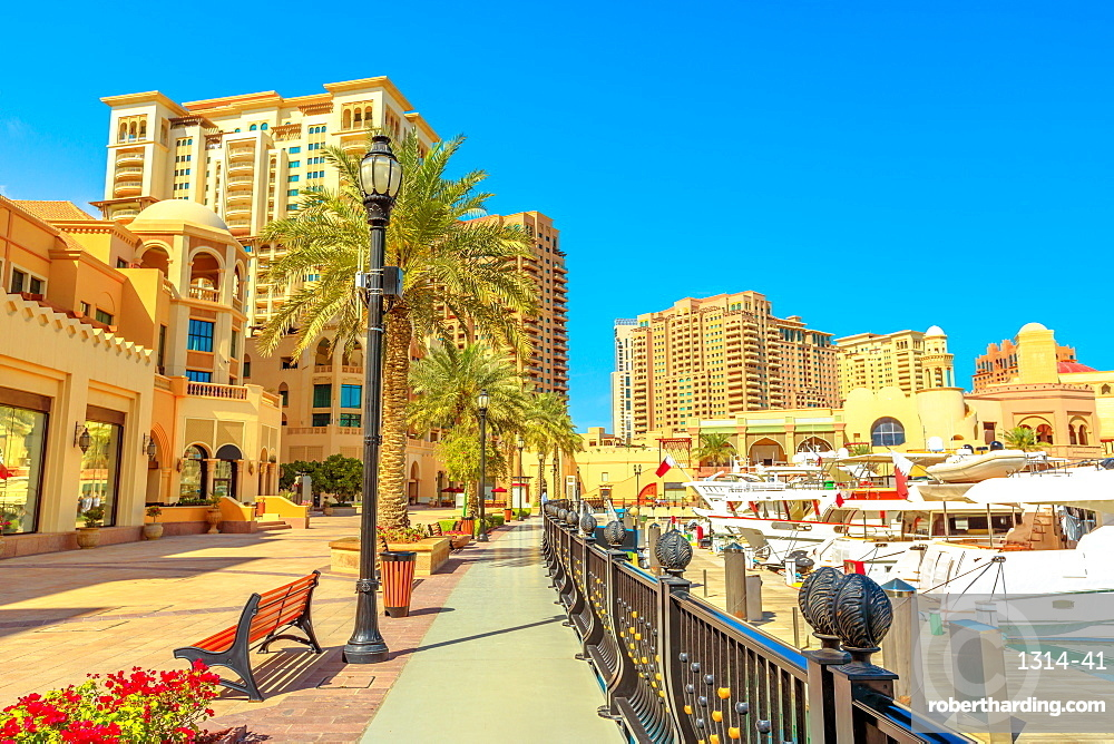 Marina corniche promenade in Porto Arabia at the Pearl-Qatar, with residential towers and luxury boats and yachts in Persian Gulf, Doha, Qatar, Middle East