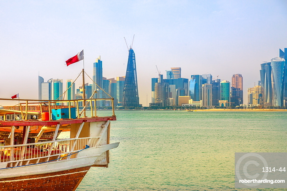 Close up of traditional wooden dhow with Qatari flag in Doha Bay in foreground and skyscraper towers of West Bay skyline in background, Doha, Qatar, Middle East