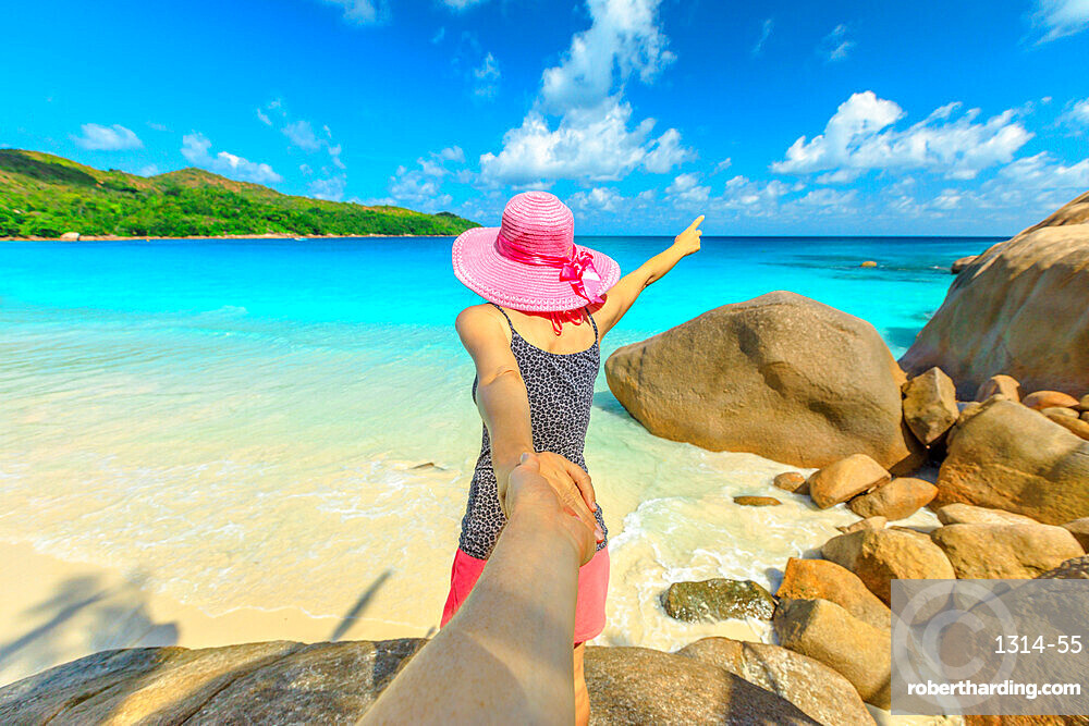 Follow me. Blonde woman holding hand of her friend at Praslin in Seychelles, Indian Ocean. Popular destination of Anse Lazio Beach surrounded by typical granite boulders. Tropical summer holidays.