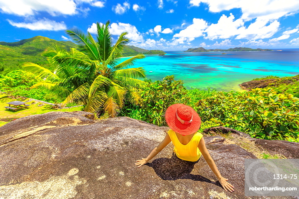 Panorama with woman looking to Cote d'Or Bay, with Curieuse, St. Pierre and Chauvre Souris Island, Anse Gouvernement, Praslin, Seychelles, Indian Ocean, Africa