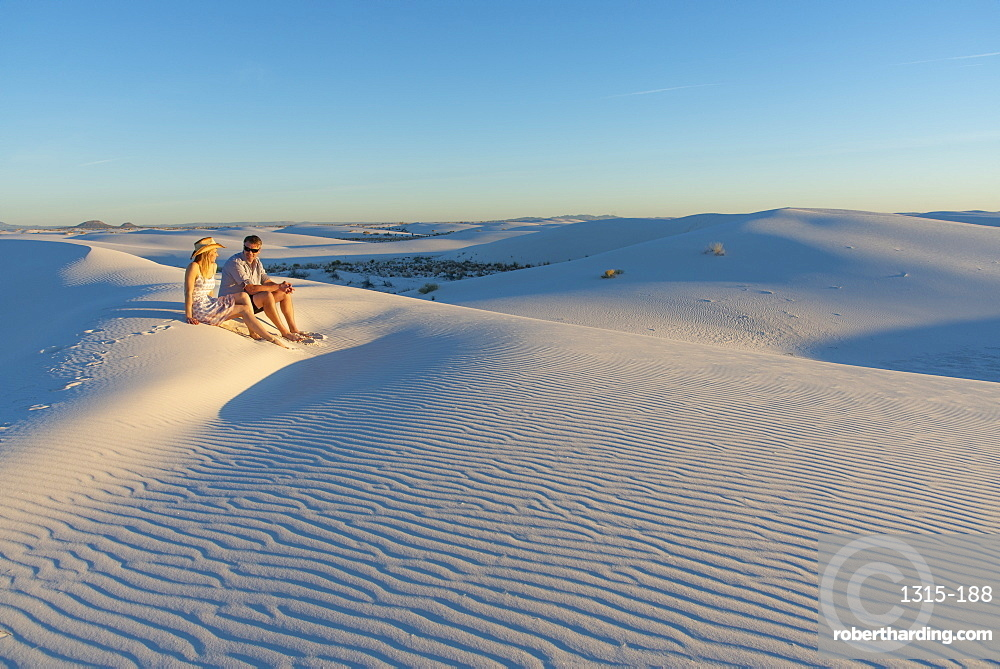 A couple enjoys White Sands National Park at sunset, New Mexico, United States of America, North America