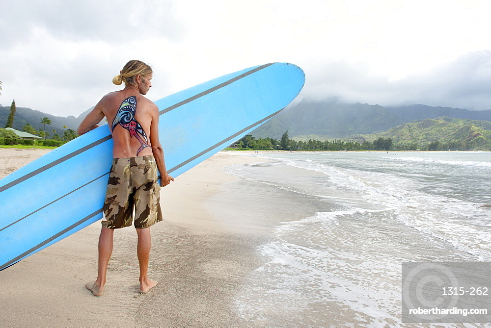 Surfer in Hanalei Bay, with a shark painted on his back, Kauai, Hawaii, United States of America, North America