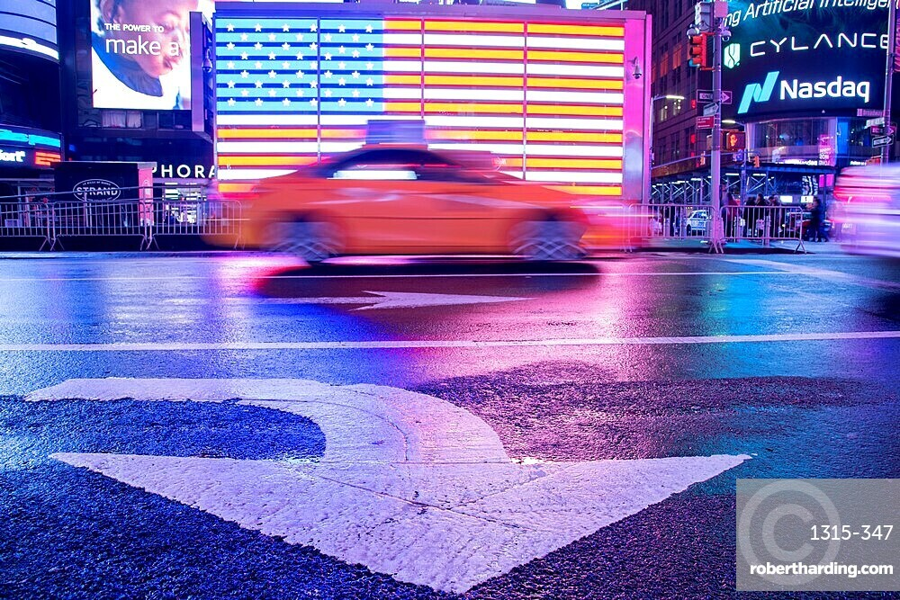 Taxi blurring by an illuminated flag of the United States of America at Times Square, New York City. Intentional motion blur.