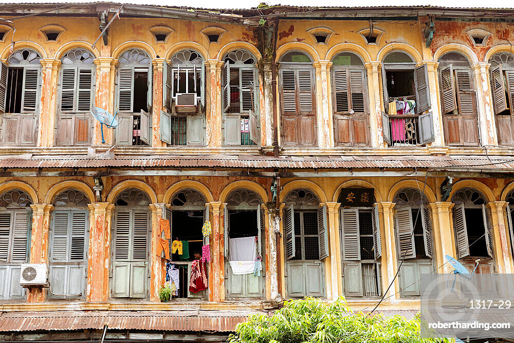The first and second floors of an old colonial apartment building in Chinatown, showing archways and wooden doors, Yangon (Rangoon), Myanmar (Burma), Asia