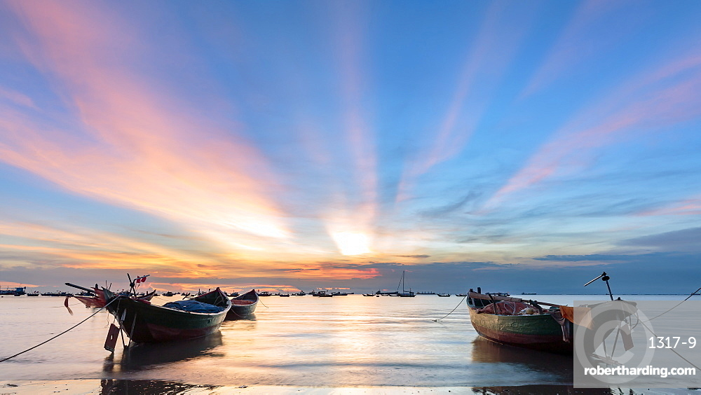 Sunset from Front beach, Vung Tau with pink clouds and small fishing boats in the foreground