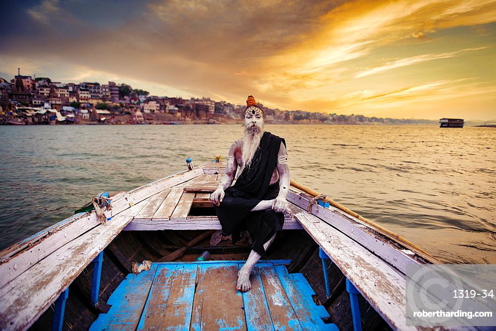 Indian Hindu Sadhu (saint) in boat on River Ganges in Varanasi, Uttar Pradesh, India, Asia