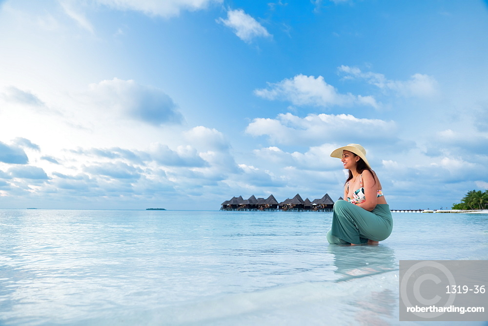 A female Indian tourist at the blue waters and white sand beach, The Maldives, Indian Ocean, Asia