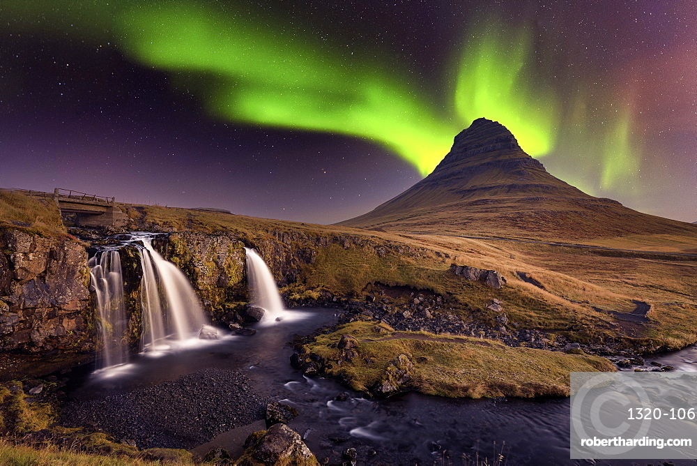 Aurora Borealis over Kirkjufell Mountian with a small waterfall in Iceland.