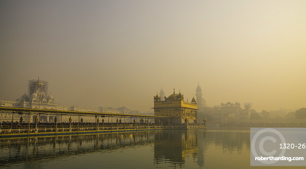 The Golden Temple at sunrise through fog. Amritsar, India