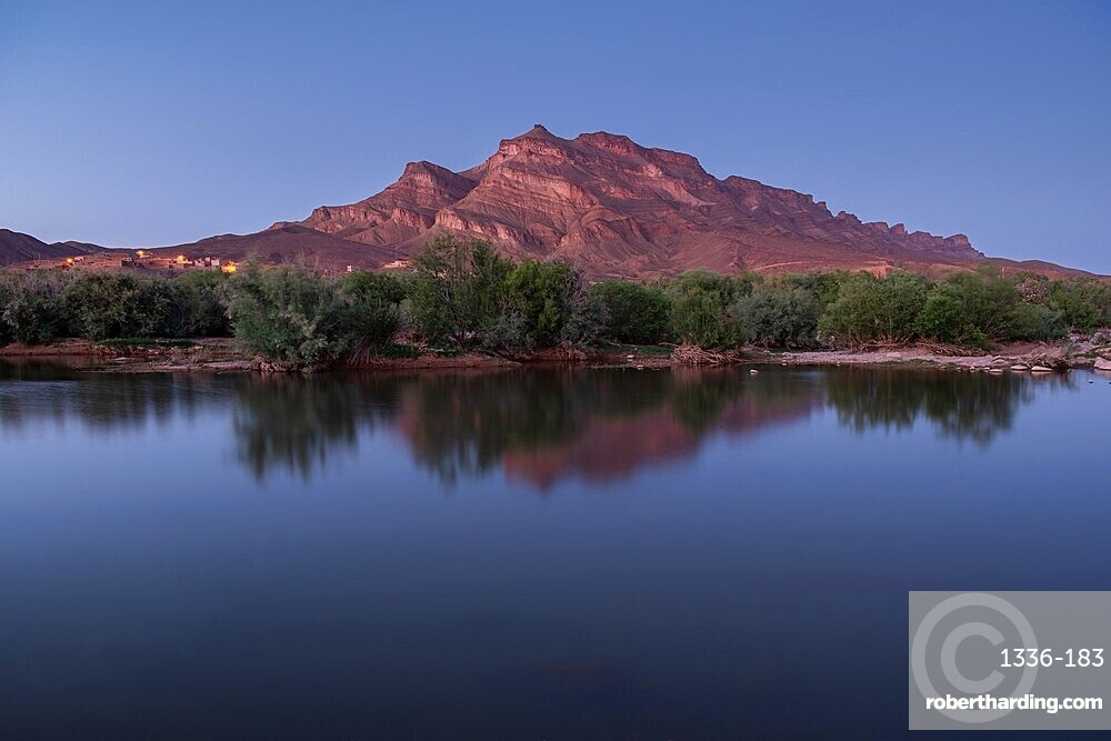 Blue hour in an oasis in the Draa Valley with a calm pond and a mountain in the background, Draa Valley, Morocco, North Africa, Africa