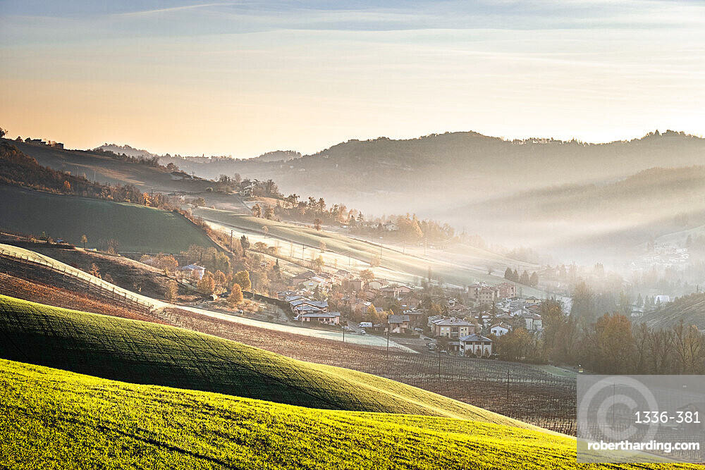 Sunrise light in the mist on gentle hills in the countryside, Emilia Romagna, Italy, Europe