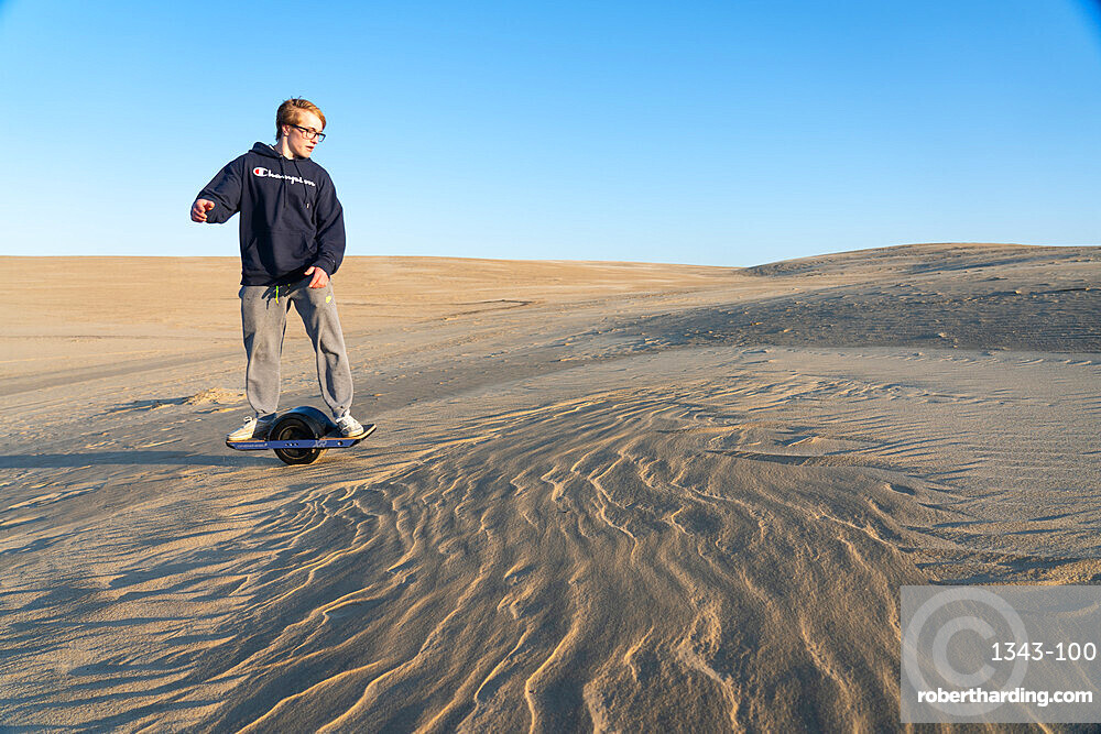 Christopher Brown rides his One-Wheel across a sand dune in Nags Head, North Carolina, United States of America, North America