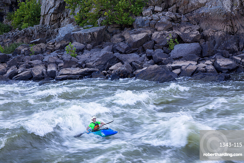 A kayaker surfs big standing waves of the Potomac River near Great Falls in his whitewater boat, Virginia, United States of America, North America