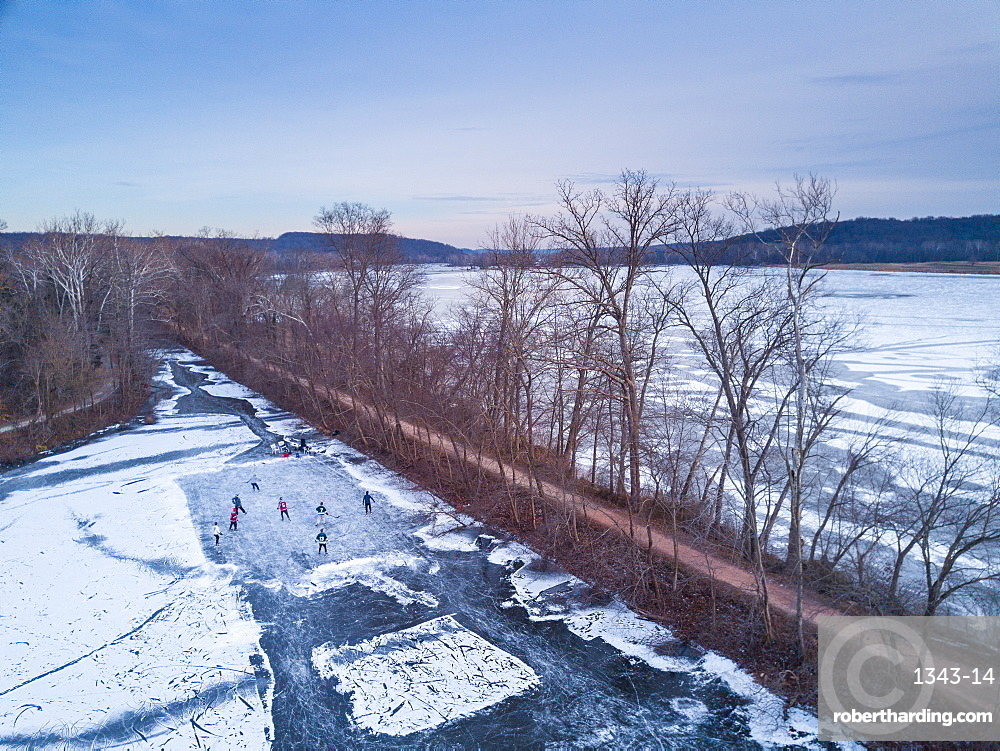 Ice skaters in a pond hockey game on the frozen C and O Canal (Chesapeake and Ohio Canal) next to the Potomac River, Maryland, United States of America, North America