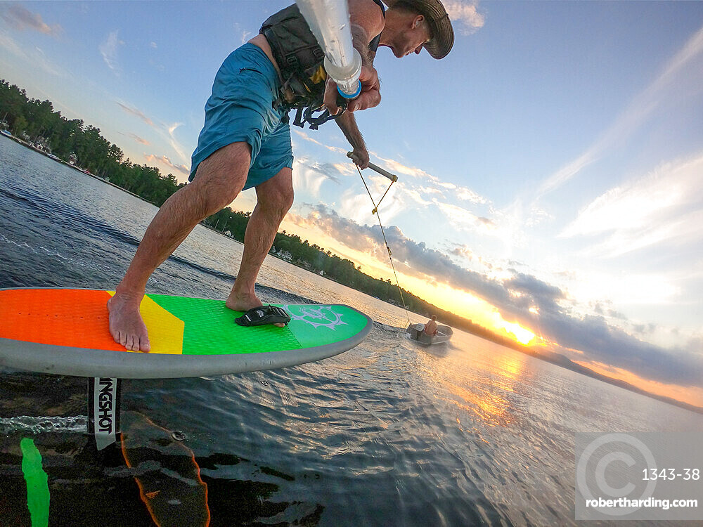 Photographer Skip Brown foils behind a small boat at sunset on Sebago Lake, Maine, United States of America, North America