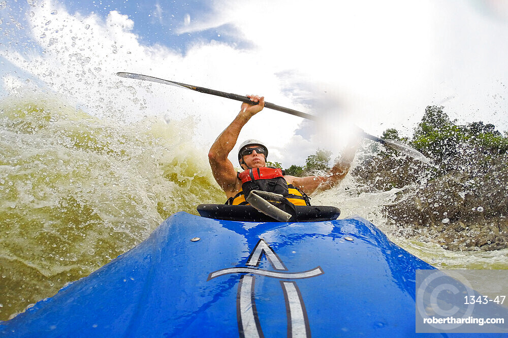 Photographer Skip Brown surfs his whitewater kayak through big water on the Potomac River below Great Falls, Virginia, United States of America, North America