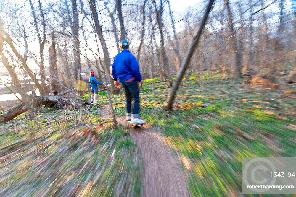 Brothers ride their One-Wheels on a single track mountain biking trail next to the Potomac River, Bethesda, Maryland, United States of America, North America