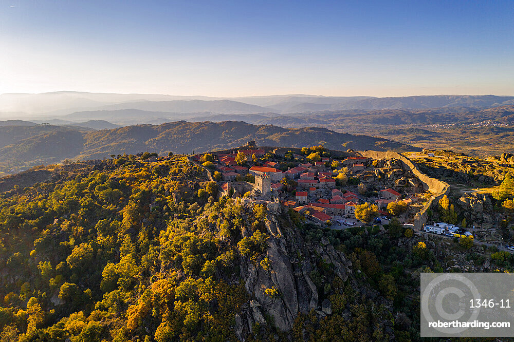 Drone aerial panorama of historic village of Sortelha with castle and with turbines on natural landscape, in Portugal