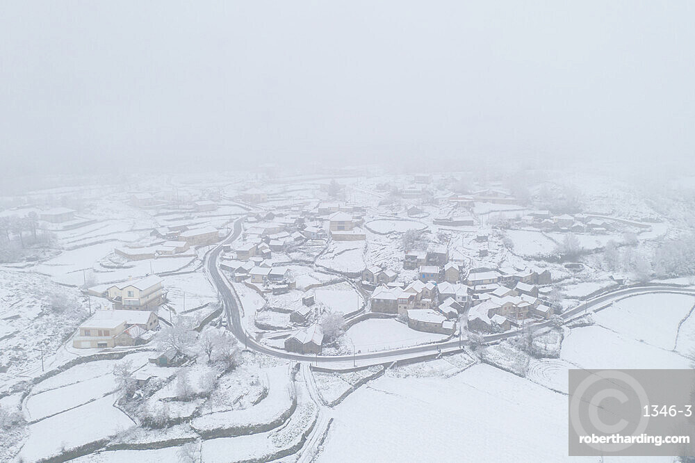 Drone aerial view of a road and remote village covered with snow in Vila Real, Norte, Portugal, Europe