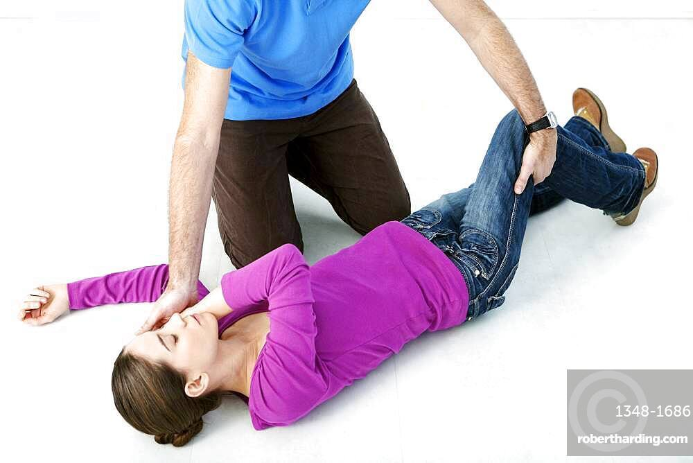 First aid techniques : placing the victim in the recovery position. Step 3 : catch hold of the leg furthest away from you behind the knee, lift it up keeping the foot on the ground. Turn the victim towards you.