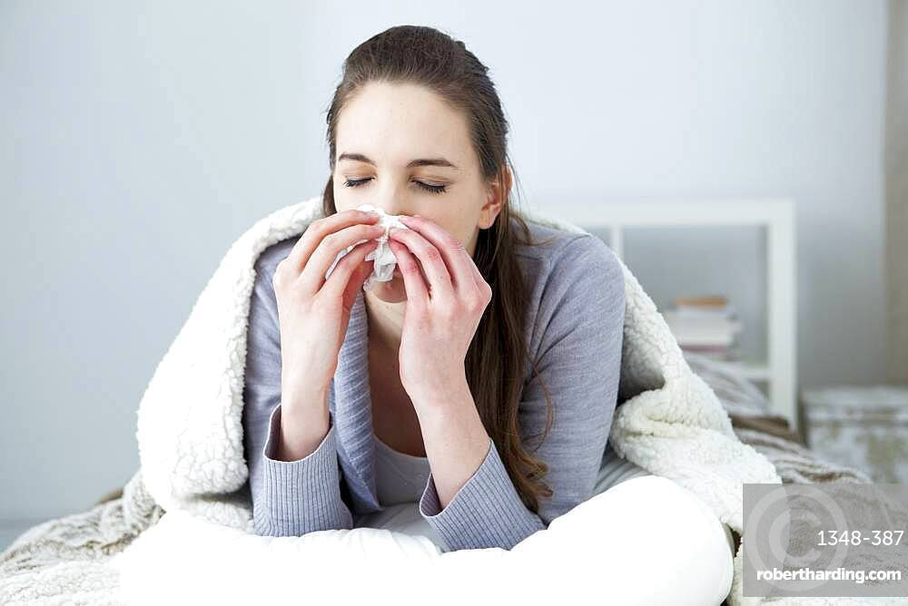 Woman blowing her nose.