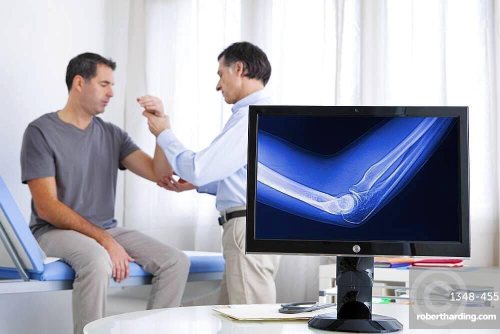 Doctor examining patient's elbow.