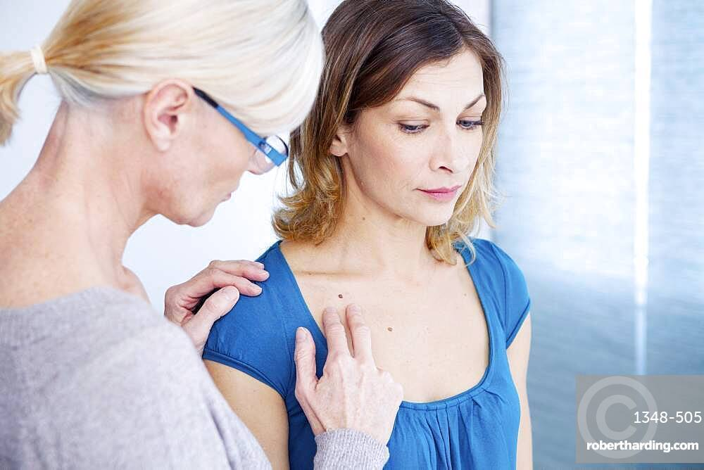 Doctor examining the upper chest of a patient.