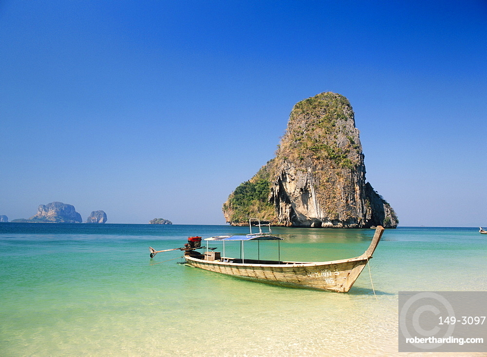 Boat moored on Phranang Beach with limestone stack behind, Krabi, Thailand *** Local Caption ***