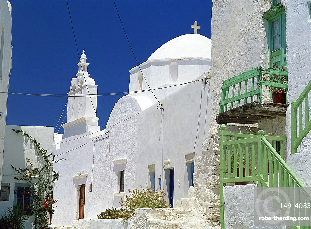 Close-up of green balcony with whitewashed walls, dome and bell tower of church beyond in The Kastro village, Folegandros, Cyclades, Greek Islands, Greece, Europe