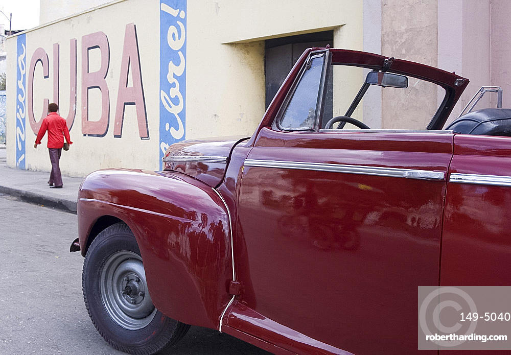 A vintage car near a 'Viva Cuba' sign painted on a wall in cental Havana, Cuba, West Indies, Central America