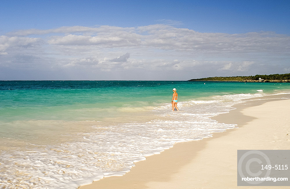 A woman walking in the surf at Playa Esmeralda, Carretera Guardalavarca, Cuba, West Indies, Central America