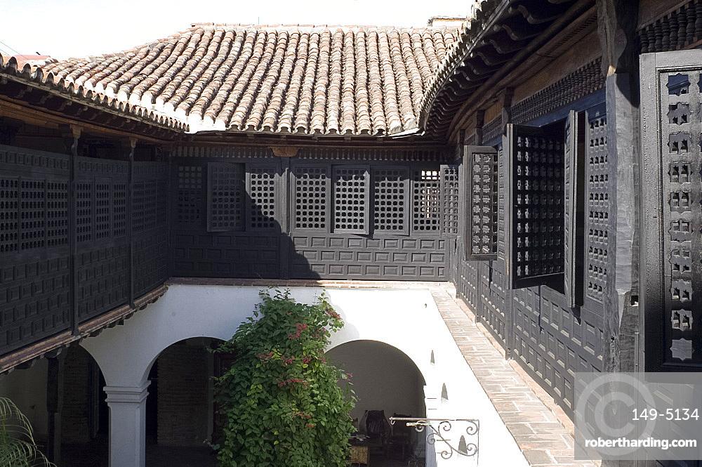 An interior courtyard surrounded by Moorish style wooden screens at the Casa de Diego Velazquez (Museo de Ambiente Historico Cubano), Santiago de Cuba, Cuba, West Indies, Central America