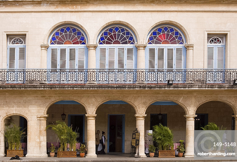 Shutters, columns and stained glass windows on the front of the Hotel Santa Isabel, Plaza de Armas, Habana Viejo,Havana, Cuba, West Indies, Central America