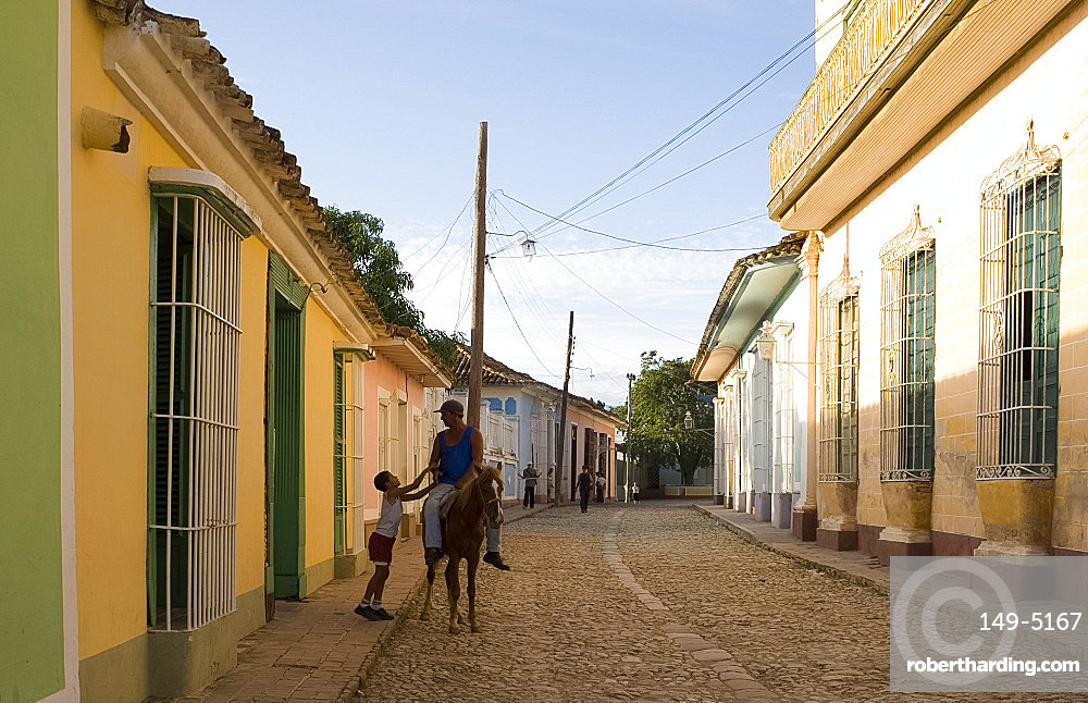 Man on horseback and boy on a cobbled street of pastel coloured houses, Trinidad, Cuba, West Indies, Central America