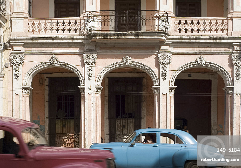 Two vintage cars passing an ornate building on Avenida Reina in central Havana, Cuba, West Indies, Central America