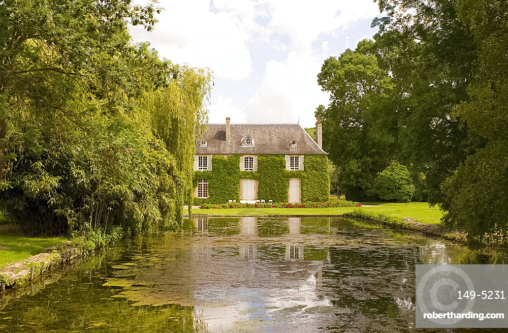 A private ivy covered house with a pond and peonies in front, Normandy, France, Europe