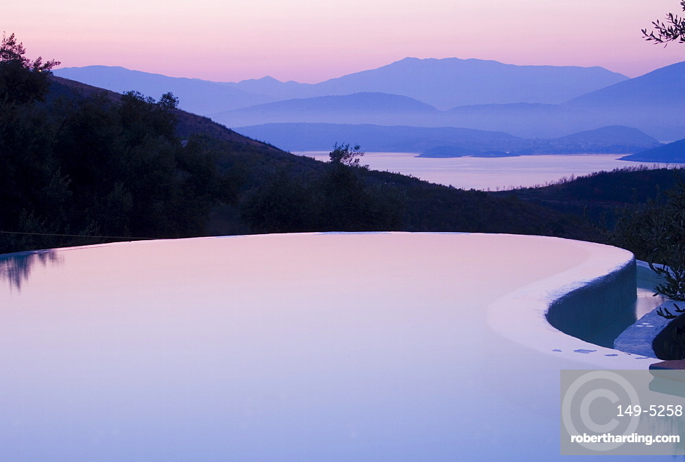 An infinity pool reflecting the sky at sunrise and the mountains of Albania across the Ionian Sea from Ayios Stefanos, Corfu, Ionian Islands, Greek Islands, Greece, Europe
