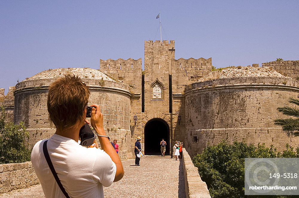 A tourist taking a photograph at D'Amboise Gate, Rhodes Town, Rhodes, Dodecanese, Greek Islands, Greece, Europe