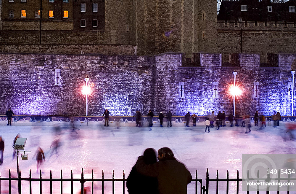 Couple watching skaters on the ice rink next to The Tower of London, London, United Kingdom, Europe
