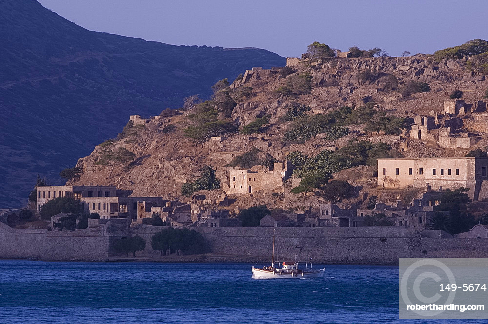 A small boat passing the island of Spina Longa, Crete, Greek Islands, Greece, Europe