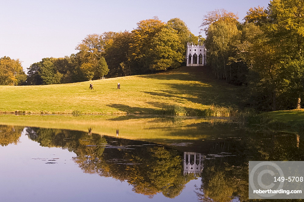 A Gothic folly reflected in the lake at Painshill Landscape Garden, Cobham, Surrey, England, United Kingdom, Europe