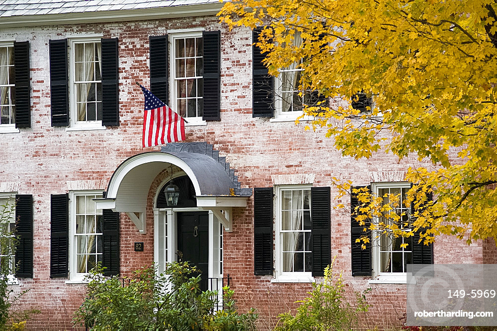 An old brick house displaying an American flag and surrounded by autumn foliage in Townshend, Vermont, New England, United States of America, North America