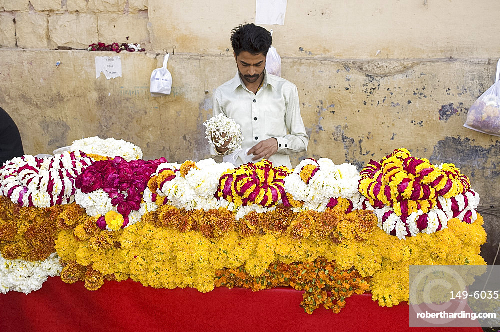 A man selling garlands of flowers outside a temple in Jaipur, Rajasthan, India, Asia