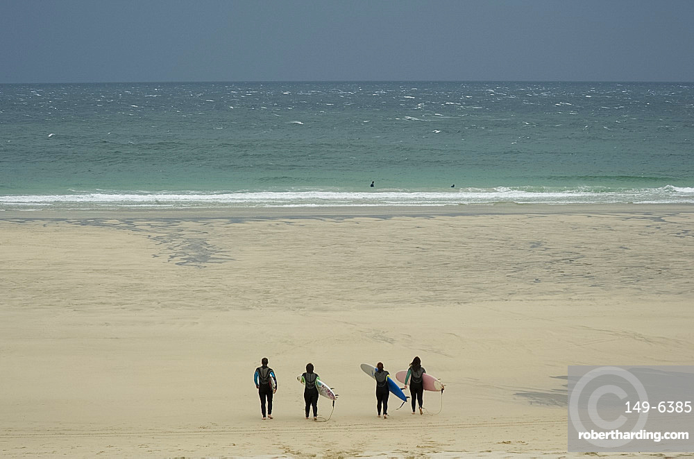 Four surfers in wet suits carrying boards and heading down the beach toward rough seas on a windy day in St. Ives, Cornwall, England, United Kingdom, Europe