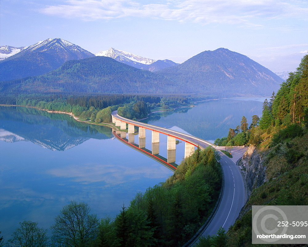 Reflections of a road bridge over Lake Sylvenstein, with mountains in the background, in Bavaria, Germany *** Local Caption ***