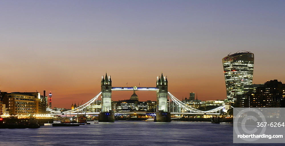 Panoramic view of Tower Bridge framing St Paul's cathedral with the City tower blocks at dusk